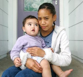 Mercedez Harrison, 1, sits with her auntie Freedom Tonihi, 12, while at home recovering from burns caused by fireworks five years ago.
