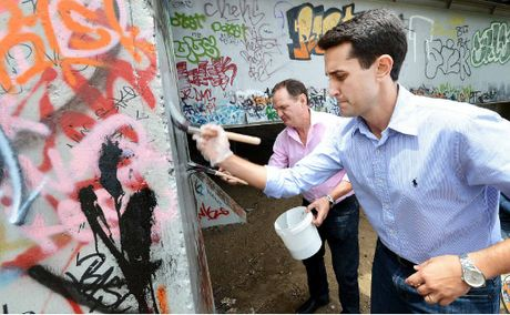 CLEAN-UP: Local Government Minister David Crisafulli (front) and Mayor Paul Pisasale remove graffiti from David Trumpy Bridge.