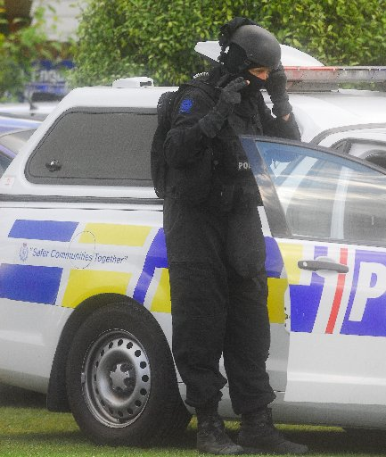 A member of the armed offenders squad prepares to search a Te Teko house.