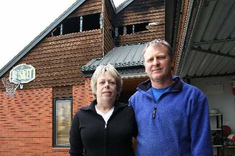"BURNT OUT: Debbie and James Kennett at their fire-damaged home in Rangiora ... youth ""needs to see what's he's done to our family home."""
