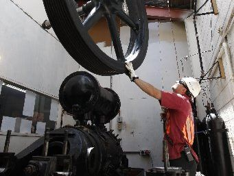 Jimmy Crowther, from Atlas Cranes, steadies the 1.5-tonne flywheel off the 104-year-old Big Bertha compressor as it is lifted through the roof of Dive HQ in Whangarei.