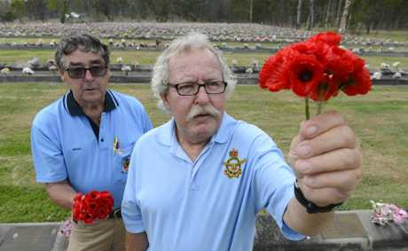 Brian Bultitude and Gerald Niland lay poppies in preperation for Remembranch Day at the lawn cemetary Photo Adam Hourigan / The Daily Examiner