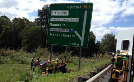 Three children were believed to be in a car which ran off the Bruce Hwy at Forest Glen, trapped the driver inside.