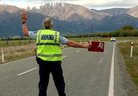 "TOO FAST: Oamaru Police Community Constable Bruce Dow pulls over a vehicle which allegedly sped past the Omarama School during ""Operation Barrel"". PHOTO/REBECCA RYAN"