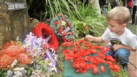 Hudson Graham, 4, pays his respects by placing a poppy flower to mark Remembrance Day at Buderim.