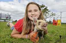 Isabelle Czernia, 9, with Blackberry a spotted piglet at the Farm Fun Open Day. Photo: Claudia Baxter / The Queensland Times
