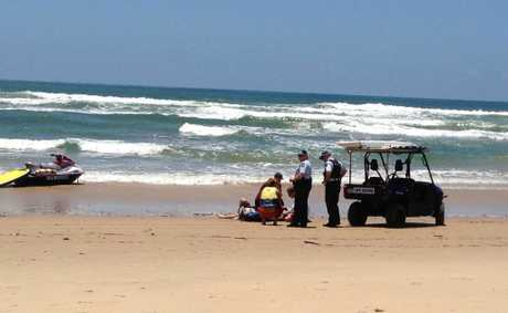 A teenage boy is treated on the beach yesterday.