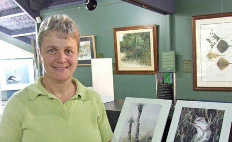 Local Artist Regina Rossdeutscher stands proudly next to her artwork.