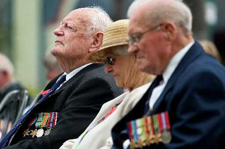Airman Max Collett (centre) and navy veteran Stan Douglas (right) reflect on the words of RSA Chaplain the Reverend Bill Chapman.
