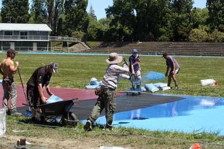CHARGING AHEAD: A group of workers busy completing the laying of the all-weather track at the Colin Pugh Sports Bowl.