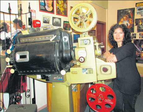 Suzanne Goodwin, the projectionist at King's Theatre in Stratford, with one of the older projectors on display in the theatre.
