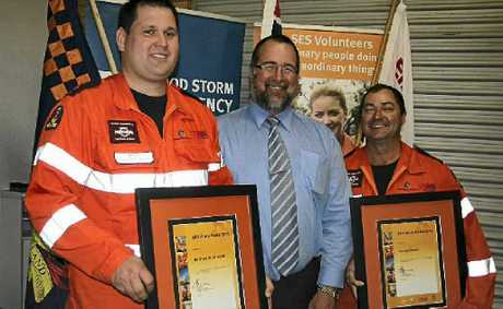 Warwick SES members Matthew Sondergeld and Vance Sinden accept their awards for extraordinary commitment from Southern Downs Mayor Peter Blundell.