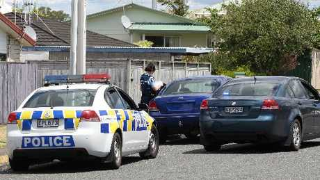 Police inspect the dark blue Ford Falcon with tinted windows and no rear number plate.