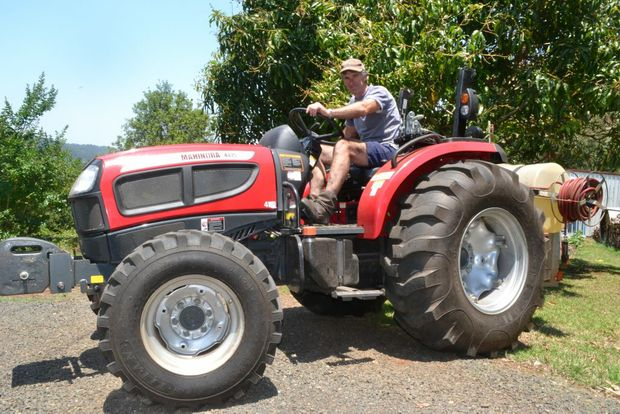 EVER PREPARED: Macadamia farmer Greg Bennett on the tractor that he used to help Rural Fire Service personnel put out spot fires. The tractor has a water tank on the back. Photo Samantha Elley/Northern Star.