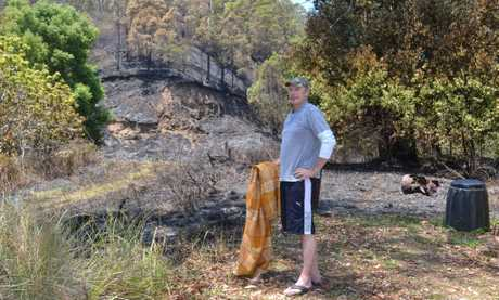 CLOSE CALL: Hamish stands at the edge of his Tuntable Creek Rd property showing how close Wednesday nights fire came. The blanket is what he used to keep the fire at bay. Below is another picture of the fire.