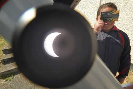CRESCENT SUN: Kororia Mulligan of Te Kura o Ratana gets a first-hand look at the eclipse from the Ward Observatory. PHOTO/STUART MUNRO