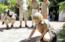 Robert Irwin puts his hands in his dads handprints at Australia Zoo.