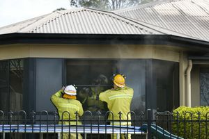Emergency workers remove the front windows of the home in order to gain better access.