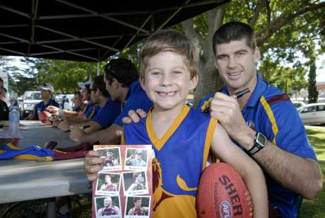 AFL fan Riley Fleming gets an autograph from Lions captain Jonathan Brown during the team's last visit to Toowoomba in 2011.