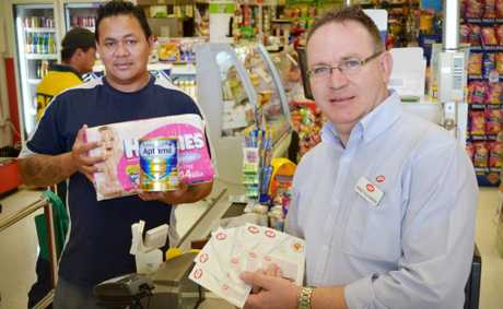 HELPING OUT: Father of three Robert Alesana is taking advantage of Westside Community Care's Christmas voucher appeal, an initiative supported by local businesses owners like Springfield IGA's Terry Slaughter. Photo: Chris Owen / The Satellite