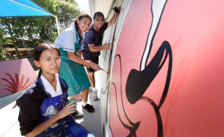 Aboriginal artist Arthur Conlon visited St Francis College and helped the kids to paint a mural, pictured with Pa Lee, 16 and Trinity Utai, 12. Photo: Inga Williams / The Reporter