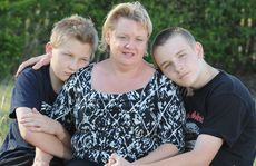 Benjamin Joynson, 13, with his mother Kim and brother Jonathon, 15, comfort each other as they remember their father and husband Willie who died in the Pike River Mine disaster in 2010.