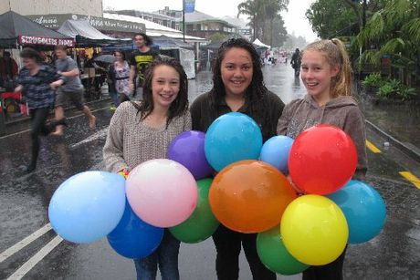 Jasmine Fegan, 14, Sophie Barnwell, 15, and Chloe Openshaw, 14, weren't about to let a little rain spoil their party - even if the downpour had others sprinting for cover. Photo / Peter de Graaf