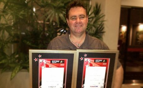 Evolution Studios owner Shayne Cantly celebrates winning two gold awards at the Queensland Media Awards.