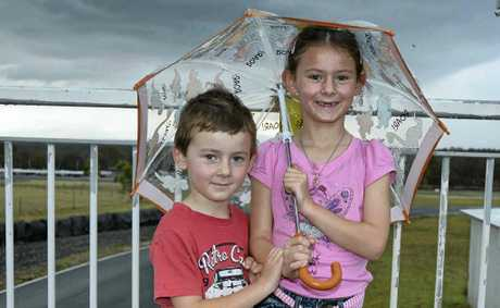 Charlie and Caitlin Bowen keep out of the rain at Morgan Park Raceway yesterday as they watch their dad in action.