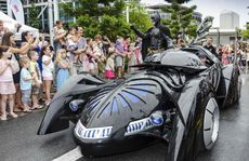 Batman arrives in his bat mobile.