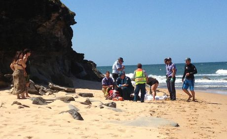 Rescuers treat a woman who fell from a cliff at Moffat Beach.