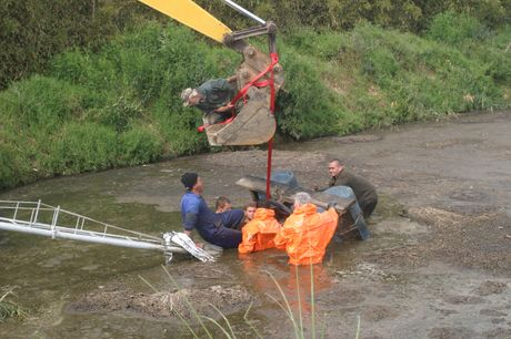 HELPING HAND: Rescuers prepare to lift the pump that trapped a farm worker (left, in the blue overalls) in an effluent pond yesterday.