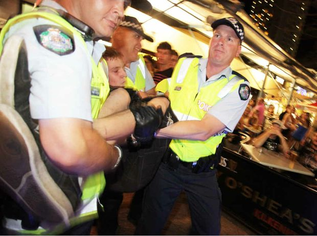 Police take a young person into custody during Schoolies on the Gold Coast.