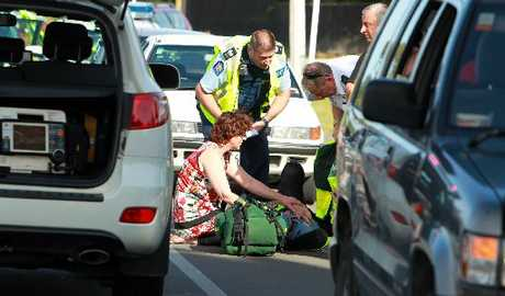 NARROW ESCAPE: A cyclist is treated by emergency staff on Te Mata Rd in Havelock North after his bike was caught between a parked car and a truck yesterday afternoon.PHOTO/ GLENN TAYLOR HBT124455-02.JPG