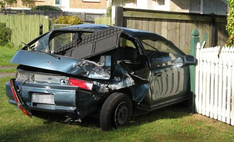 BADLY DAMAGED: The impact of the accident sent the Toyota crashing through the fence.