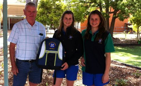 JETSETTERS: Murgon Lions member Bevan Routledge presents the girls with their uniform for the trip. 