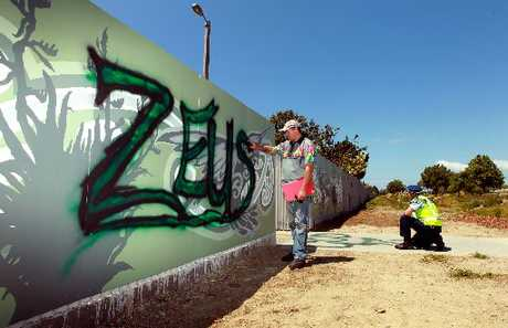 PUTTING IT RIGHT: Tag removal specialist Graffiti Doctor Phil Duffy prepares to eliminate the tagging defacing a mural beside the new Harakeke Walkway in Napier less than four days after the artwork was put in place.