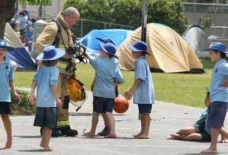 INJURED: A firefighter speaking to school kids at Mayfair School on Tuesday after a gas canister exploded, burning the arm of a parent.