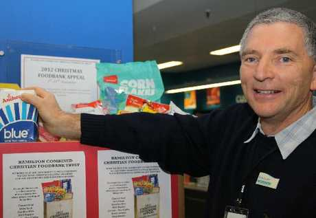 FESTIVE FOOD: Hamilton City Libraries&#39; heritage team leader Mark Caunter adds to a collection box designed to bolster foodbank shelves ahead of Christmas. All city libraries are participating.
