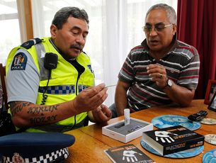 Bill Taua shows James Ranginui how the kit works during the police visit to the Fairfield area.