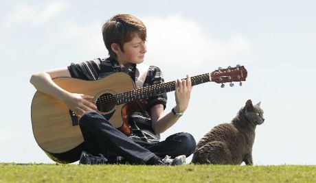 MUSIC MAN: Oropi 12-year-old Fletcher Oxford strums a tune to his new cat Zoe. He took up singing and songwriting after his previous pet  Sushi went missing.