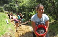 Young Frenchwoman Charlotte Cristofari helps to lug 6 cubic metres of gravel up the hill.