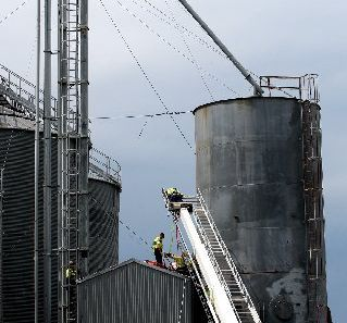 Emergency services winch a 30-year-old man from the the top of a shed after he fell 30m from a tower at the PGG Wrightson Seed and Grain Centre in an industrial part of Hastings.