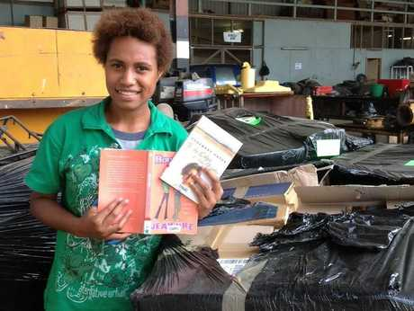 Vanessa Andy, a student in Papua New Guinea, admires the donated books. Photo: Contributed