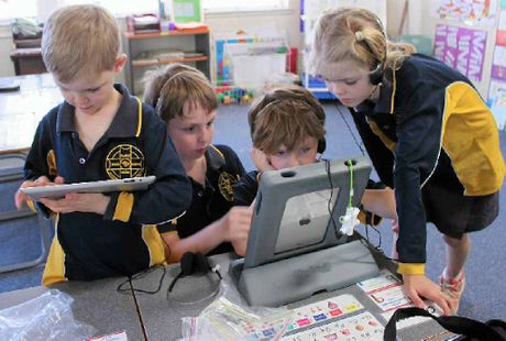 SNAILS PACE: Clarke Creek State School students Cameron Hill, 6, Max, 9 and Franko Deveson, 7 and Lydia Hill, 9, use the school iPads but internet speeds limit what they can do online.