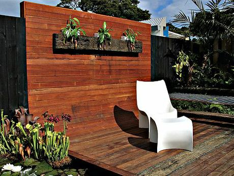 This deck, although freestanding, creates its own sense of enclosure by curving up at the back. Railway sleepers have been inserted into the new decking as a planter on the back wall, and as an insert in the floor of the deck. 