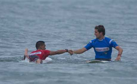 Harley Ingleby in blue congratulates Hawaii's Nelson Ahina after Ingleby was defated in the quarter finals of the ASP World Longboard Titles.