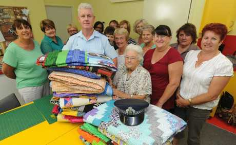 Senior Sergeant Dan Willett accepts 22 quilts for Police Legacy from Hervey Bay Social Quilters including the group&#39;s oldest member Joyce Murphy.