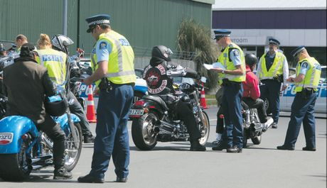 Police check motorcyclists on Birch Ave as they head to the Filthy Few clubhouse after the funeral of Filthy Few member Dennis &quot;Deno&quot; Pedersen.
