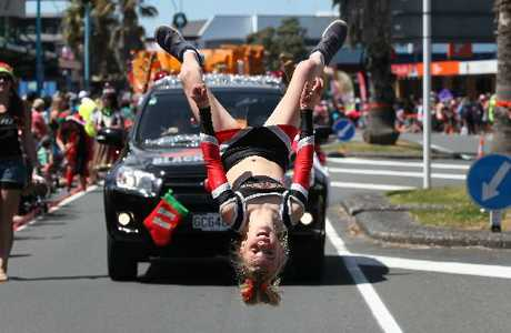 A gymnast with the ZM Black Thunder car wows the crowd during the TrustPower and Mount Mainstreet Christmas Festival and Santa Parade.